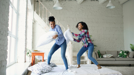 Mixed race young pretty girls jumping on bed and fight pillows having fun at home