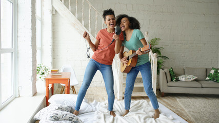 Mixed race young funny girls dance singing with hairdryer and playing acoustic guitar on a bed. Sisters having fun leisure in bedroom at home