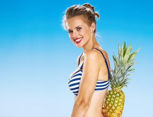 smiling young woman on seacoast hiding pineapple behind back
