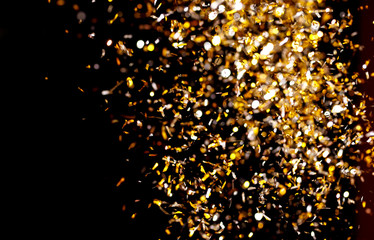 Photo of golden confetti on black background.