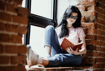 Beautiful young brunette woman reading book near window at home.