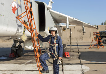 Military pilot in helmet stands near jet plane