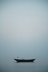 An empty old fishing boat in the calm water of the sea