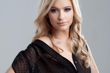 Young and attractive blonde girl with shiny wavy hair . Beautiful model, curly hairstyle .