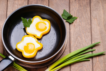 Bell pepper egg rings on a cooking pan, parsley and green onion