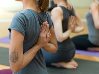 Women practicing yoga: reverse prayer pose