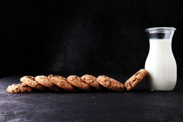 Chocolate chip cookies with milk on dark grey table