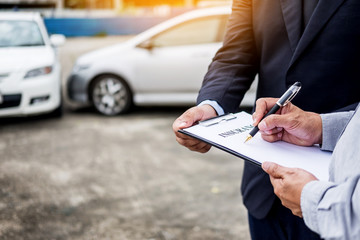 Car insurance agent send a pen to his customers sign the insurance form on clipboard while examining car after accident claim
