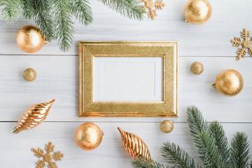 Top view of gold luxury blank frame, with gold decoration ball, gold ornament snowflake, pine brance on white wood table top,Flat lay , holiday celebration still life,mock up for adding text,copy spac