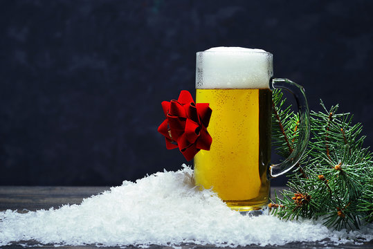 Glass mug of beer in the snow on a dark background.