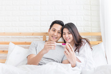 Happy couple hugging with positive pregnancy test in bedroom.
