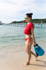 Young brunette woman, girl at the beach in red bikini walking with waterproof blue bag and sun glasses. Asia, Thailand
