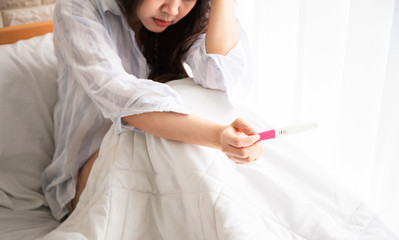Selective focus Pregnancy test positive result on hand of  woman sitting on bed in her bedroom. Pregnancy is not ready concept.