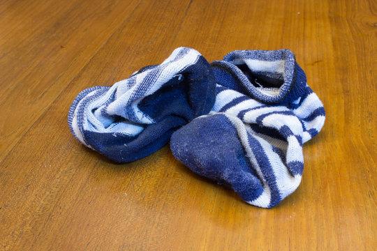 Dirty Blue Stripes Socks Left on Wooden Floor.