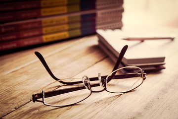 Vintage glasses with stack of books.