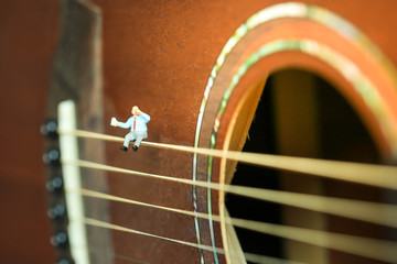 Miniature people : Businessman sitting on acoustic guitar. time of relax or music relax concept.