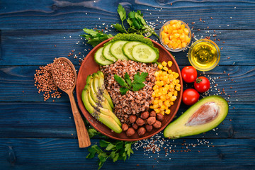 Healthy food. Buckwheat, avocado, cucumber, corn and hazelnut. On a wooden background. Top view. Free space for your text.