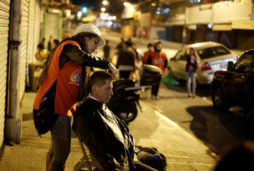 A volunteer from the Association of the Holy Spirit gives a man a haircut  during an event held to celebrate Christmas for homeless people, in San Jose