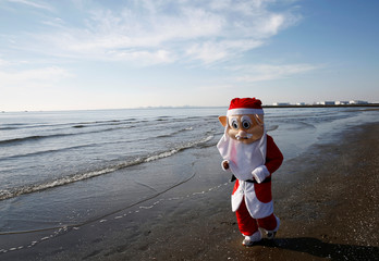 "A participant dressed up as Santa Claus runs on the beach during the annual charity run event known as ""Tokyo Santa Run"" in Chiba"