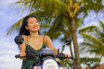 happy and pretty Asian Chinese woman having fun riding scooter  motorbike on tropical Summer palm tree background smiling cheerful