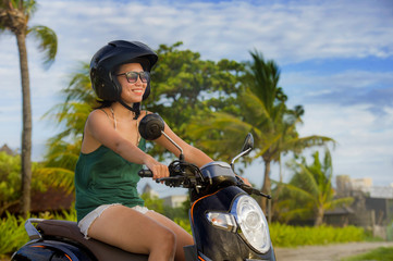 young happy and pretty Asian Chinese woman riding scooter wearing safety motorcycle helmet having fun on tropical Summer background