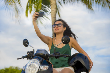 young happy and pretty Asian Chinese woman taking selfie portrait picture with mobile phone camera riding scooter motorbike
