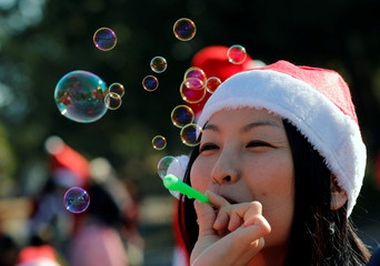"A participant dressed up as Santa Claus blows bubbles before the start of the annual charity run event known as ""Tokyo Santa Run"" in Chiba"