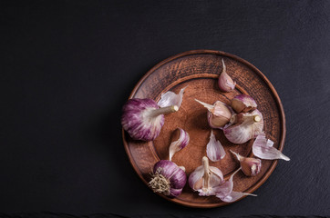 garlic in the plate on black stone table / top view/