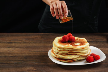 Chef pours pancakes with honey, hands close-up. Beautiful food still life. Dark black background, natural light. The concept of cooking, cooking. Copy space.