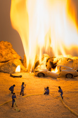 Miniature firefighters at a car accident scene in flames
