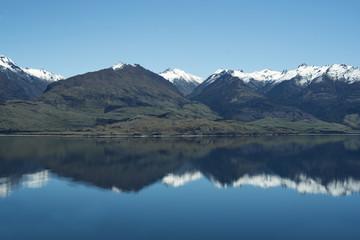 Fotorollo Reflexion Paisaje de montañas frente a un gran lago donde se reflejan. Cielo azul despejado.