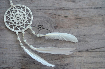 Dreamcatcher on a shabby wooden background. Ethnic design, boho style, tribal symbol