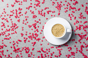 A cup of coffee, small red hearts over stone  on background. St. Valentine's day concept. Top view, copy space.