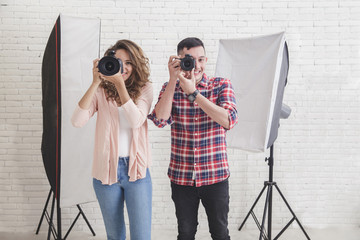 young man and woman taking photo with professional camera