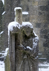 snow falling an a graveyard statue of a mourning woman holding a cross