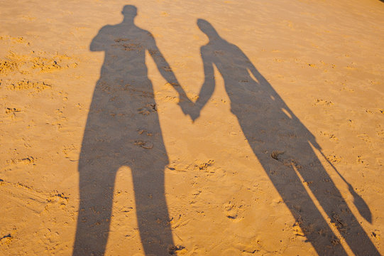 Portugal, Albufeira,  portuguese beach with cliffs PRAIA DA GALA, couple hold hands shadow on sand