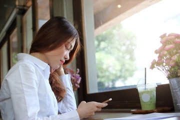 Attractive young Asian woman looking mobile smart phone in coffee shop.
