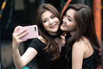 Two friends taking selfie together in pub in early evening. Two beautiful chinese woman taking selfie together with sexy posture before posing to social media. Party and online presence concept.