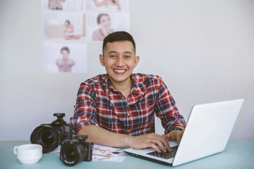 young photographer sitting on his office while working on laptop