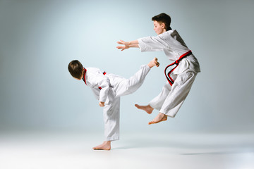 Studio shot of two of kids training karate martial arts