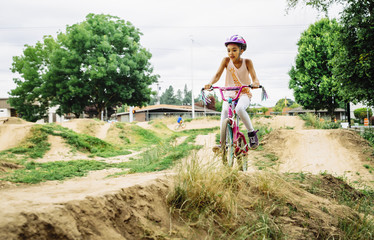 Girl riding dirt bike on course