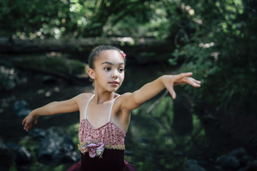 Girl doing ballet pose in forest