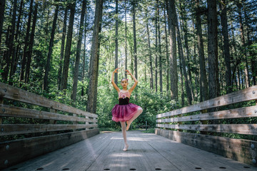 Girl wearing tutu practicing ballet pose in forest