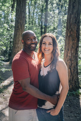 Portrait of happy mixed race couple in forest