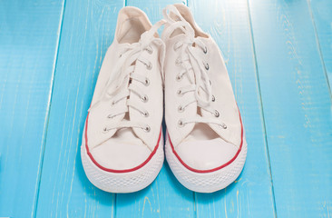 A pair of new white hipster sneakers on a wooden background