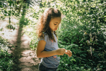 Girl looking at leaf in forest