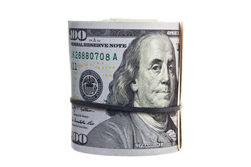 A large roll of hundred dollar bills knitted by a black rubber band isolated on white background.
