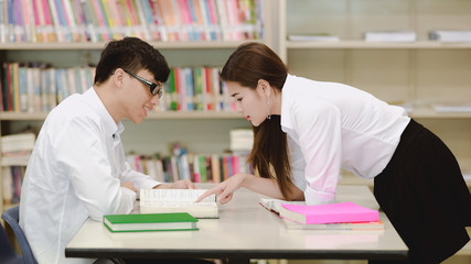 Young students study hard in library. Happy Asian female and male university students doing study research in library with books on desk, notebook. For back to school education diversity concept.