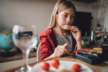 Wall Mural - Girl wearing red hoodie eating sandwiches and using tablet