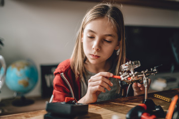 Girl using multimeter and learning robotics